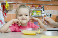 Girl eating porridge in the kitchen Stock Images