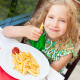 Girl eating potato chips in the cafe Stock Photos