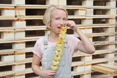 Girl Eating Potato Chips On A Stick. Junk Food, Street Food, Snack On A Walk. Stock Image