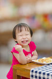 Girl eating puff by herself and smile Stock Photos