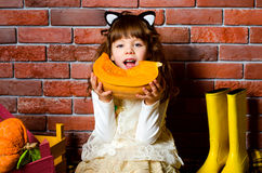 Girl eating a pumpkin. Girl in the cat's ears eating pumpkin Stock Photo