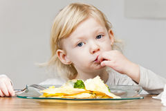 Girl eating quesadilla Stock Images