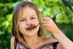 Girl eating raspberry Royalty Free Stock Images