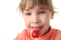 Girl eating red lollipop, half body, front view Stock Images