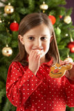 Girl Eating Reindeer Shaped Cookie In Front Of Tre royalty free stock images