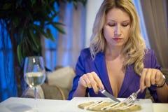Girl eating in a restaurant. Beautiful girl eating in a restaurant stock photography