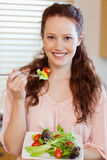 Girl eating salad. Girl eating fresh salad in the kitchen Royalty Free Stock Image
