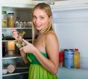 Girl eating salad from fridge Stock Images