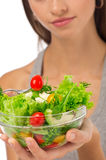 Girl eating salad sitting on her bed Stock Photo