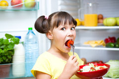 Girl eating salad standing near refrigerator Stock Photos
