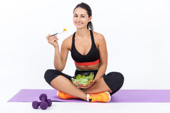 Girl eating salad after training Royalty Free Stock Photo