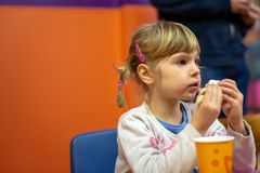 Girl eating sandwich at birthday party stock photo