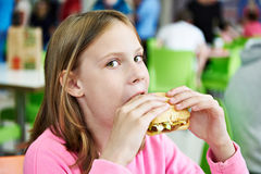 Girl eating sandwich in cafe Stock Photography