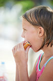 Girl eating a sandwich Stock Images