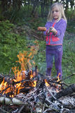Girl Eating Sausage Cooked On Camp Fire Royalty Free Stock Photography