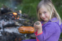 Girl Eating Sausage Cooked On Camp Fire Royalty Free Stock Images