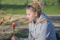 Girl eating sausage from the grill. Outdoors on the green grass camping stock photos
