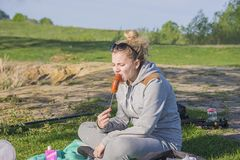 Girl eating sausage from the grill. Outdoors on the green grass camping royalty free stock image