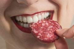 The girl is eating sausage. A piece of sausage in the mouth of a woman. Business concept is the brand`s appeal. Appetite. The girl is eating sausage. The woman Stock Photo