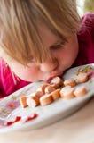 Girl eating sausages Stock Image