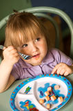 Girl eating sausages. Young girl sitting at a table and eating sausages from a colorful plate Royalty Free Stock Images