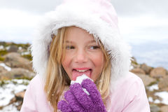 Girl eating snow. A gorgeous little girl delights in eating snow Royalty Free Stock Image