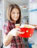 Girl eating soup from pan near fridge royalty free stock image