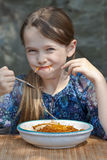Girl is eating spaghetti. Seven year old girl is eating spaghetti outside Stock Photos