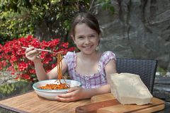 Girl is eating spaghetti. Seven year old girl is eating spaghetti outside Royalty Free Stock Photography