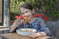 Girl is eating spaghetti Royalty Free Stock Image