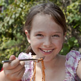 Girl is eating spaghetti. Seven year old girl is eating spaghetti outside Stock Photo