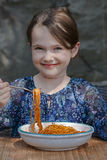 Girl is eating spaghetti. Seven year old girl is eating spaghetti outside Stock Image
