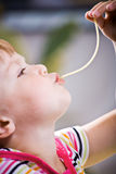 Girl eating spaghetti Stock Image