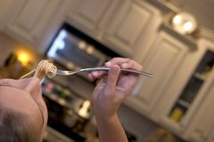 Girl eating spaghetti from fork Stock Photos
