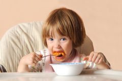 Girl eating spaghetti sitting in highchair Stock Images