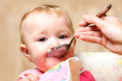 Girl eating from spoon Stock Photography