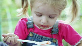 Girl eating with spoon stock footage