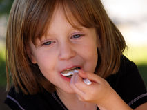 Girl eating spoonful. A happy little girl enjoys a spoonful of ice cream Royalty Free Stock Images