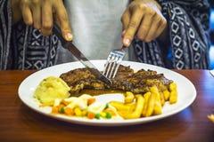 Girl eating a steak. Stock Images