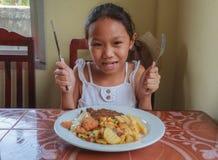 Girl eating Steak. Young girl holding a steak knife and fork eating steak in restaurant Royalty Free Stock Photos
