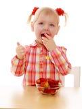 Girl eating strawberries Royalty Free Stock Image
