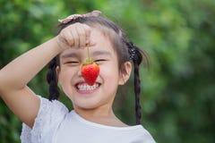 Girl eating strawberries Royalty Free Stock Photos