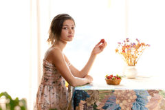 Girl eating strawberries sitting at table indoor Royalty Free Stock Images