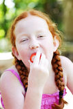 Girl eating strawberry. Portrait of ginger haired girl eating strawberry outdoors Stock Image