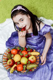 Girl eating strawberry. Little girl eating strawberry from a fruit basket stock photos