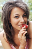 Girl eating a strawberry. Beautiful young girl eating a strawberry royalty free stock images