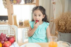 Free Girl Eating Strawberry At Breakfast Table Stock Images - 149145904
