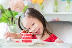 Girl eating strawberry cake at home. Little asian girl eating strawberry cake at home Royalty Free Stock Photos