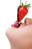 Girl eating strawberry with chocolate sauc Stock Images