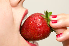 Girl eating strawberry closeup Stock Photo